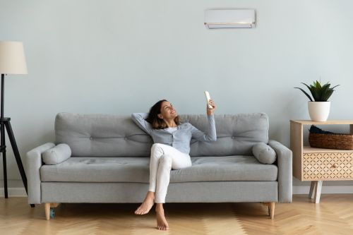 Woman turning on airconditioner