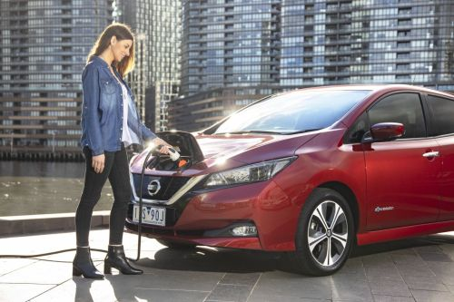 Woman standing next to a Nissan Leaf