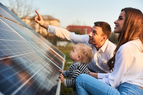 A family looking at a solar panel