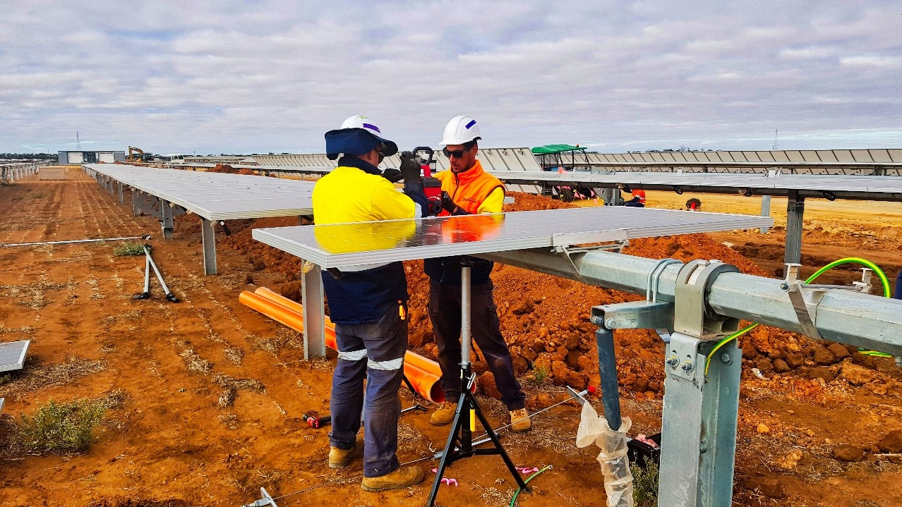 Men wearing hardhats working on a solar construction site